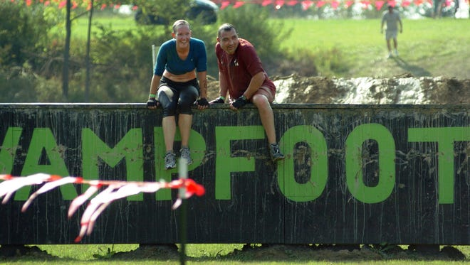 Joyce Koncz takes a break on the wall with her husband Andrew Khan, both of Sterling Heights during the Swampfoot 4 Mile race.