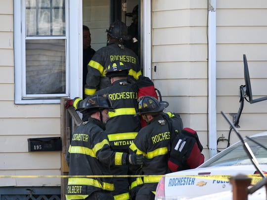 Rochester firefighters enter a house in January to help extricate  four bodies that were found in a burning house at 193-195 Leighton Ave.