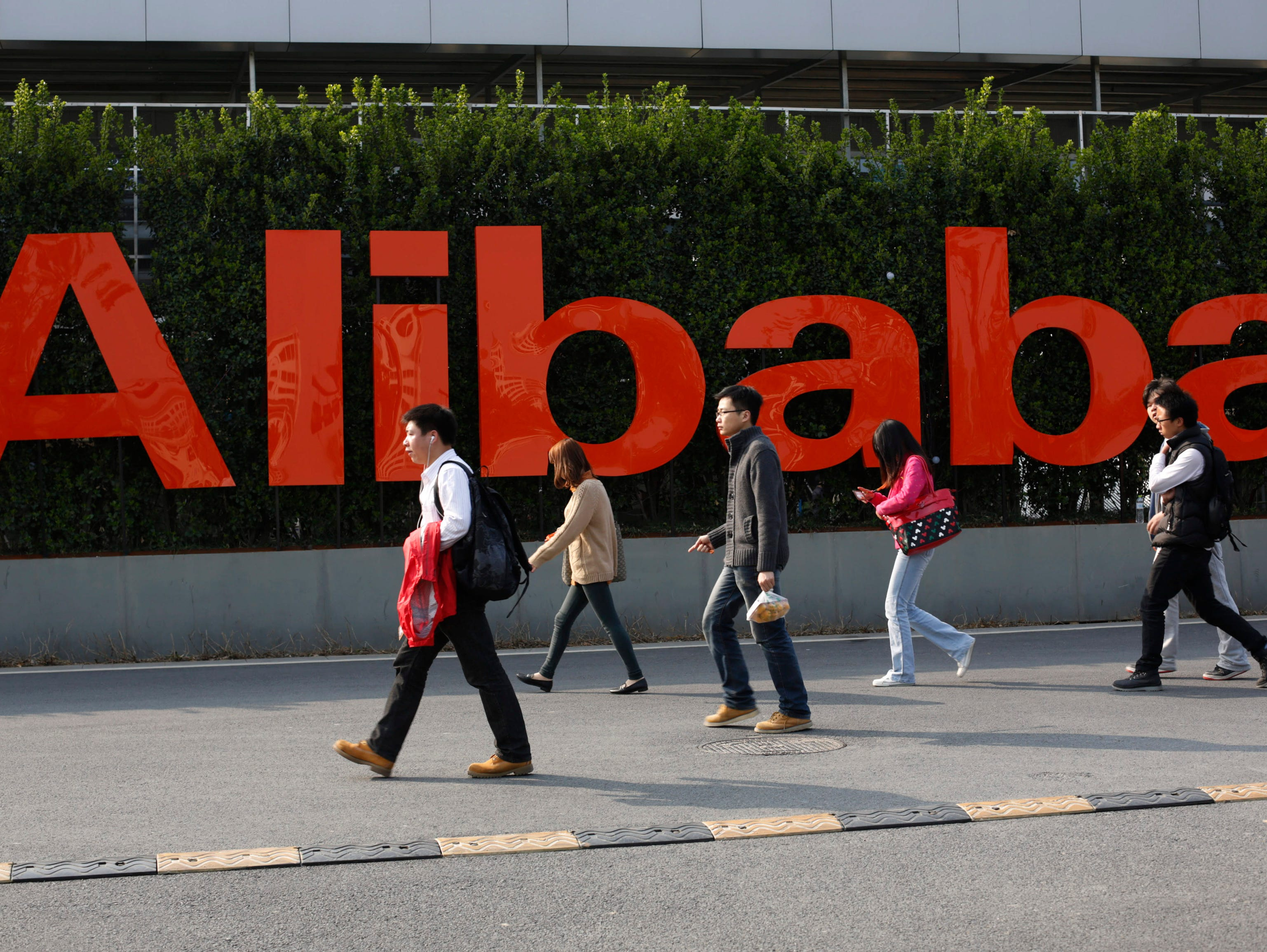 People walk past a company logo at the Alibaba Group headquarters in Hangzhou in eastern China's Zhejiang province.