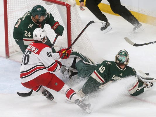 Carolina Hurricanes' Teuvo Teravainen, front left, chases after the puck after Minnesota Wild goalie Devan Dubnyk, right, blocked a shot during the first period of an NHL hockey game Tuesday, March 6, 2018, in St. Paul, Minn. (AP Photo/Jim Mone)