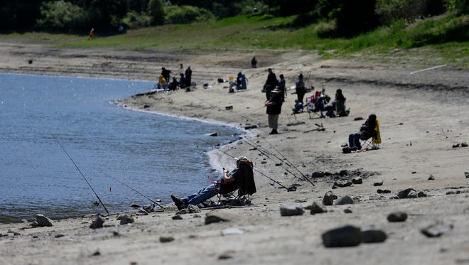 People fish at San Pablo Reservoir Recreation Area in El Sobrante, Calif., on Thursday, April 2, 2015. A spokeswoman for the East Bay Municipal Utility District said that the reservoir is about half full.