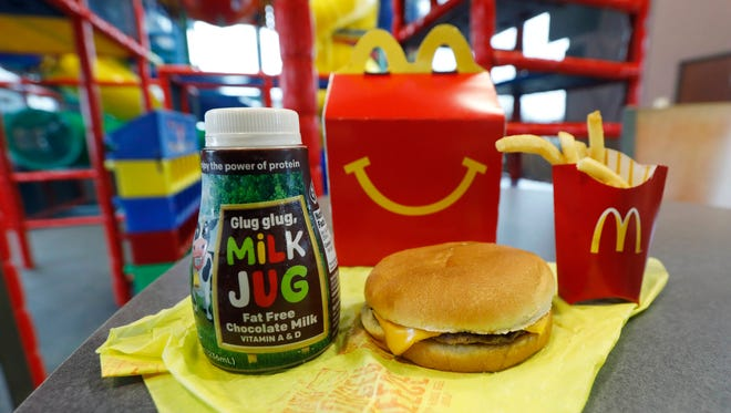 A Happy Meal featuring non-fat chocolate milk and a cheeseburger with fries, are arranged for a photo at a McDonald's restaurant in Brandon, Miss., Wednesday, Feb. 14, 2018. McDonald's will soon banish cheeseburgers and chocolate milk from its Happy Meal menu. Diners can still ask specifically for cheeseburgers or chocolate milk with the kid's meal, but the fast-food company said that not listing them will reduce how often they're ordered. (AP Photo/Rogelio V. Solis)