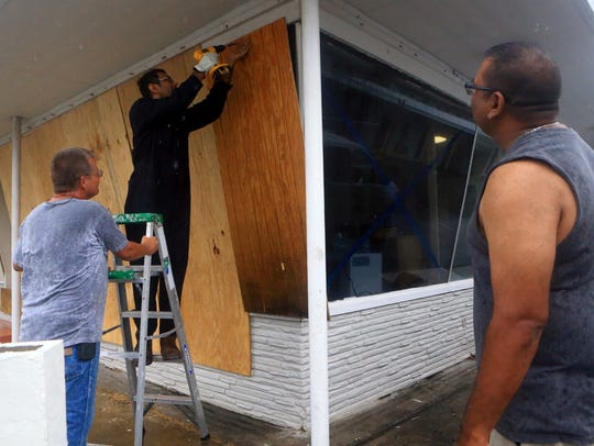 Vimal Patel (center) boards up windows with the help