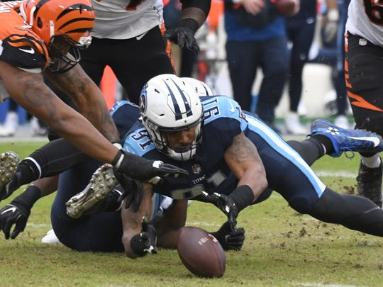 Titans linebacker Derrick Morgan (91) picks up a fumble after Bengals quarterback Andy Dalton (14) lost the ball after being hit.