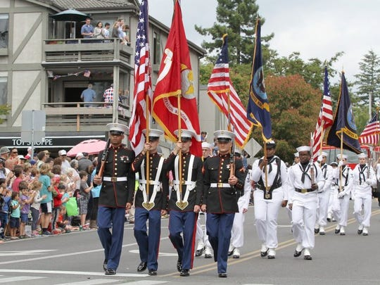 A Marine color guard leads the Grand Old Fourth Parade down Madison Avenue in Winslow. (Steve Zugschwerdt / Special to the Kitsap Sun)