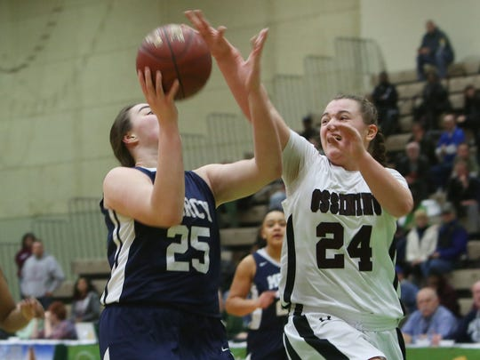 Ossining's Kelsey Quain (24) blocks a shot against Our Lady of Mercy in the girls basketball Class AA state semifinal game at Hudson Valley Community College in Troy on March 17, 2017.