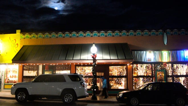 Diane's Restaurant lights up the night with Christmas decorations under a full moon on Wednesday in Silver City. Last minute shoppers and early evening diners were out keeping Bullard Street bustling.