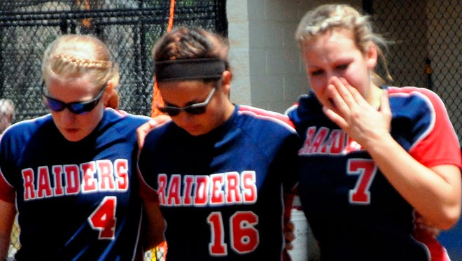 Lakota's Sam Miller (No. 4), Nikkia Cooper (16) and Morgan Gangwer (7) comfort one another following the Raiders' 6-2 loss to New Riegel in the Division IV regional championship game Saturday at Findlay High School.