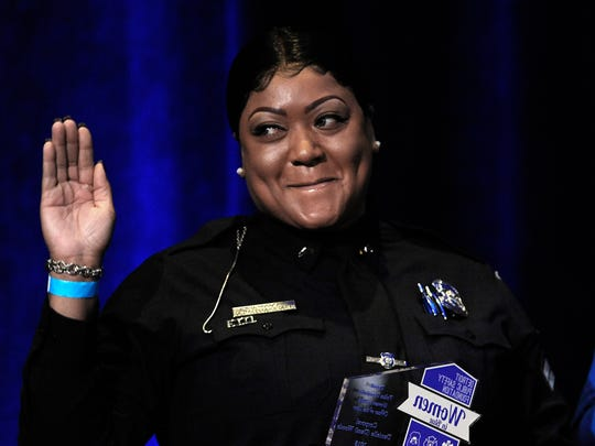 DPD Corporal Danielle Woods waves at the audience as she receives her department's Woman in Blue Officer of the Year.