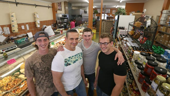 Dominic Mammoliti, second from left, surrounded by his sons, Dom Jr., left, Will, right, and Alex at Dominic's Calabresella Deli in Gates on June 9, 2017.