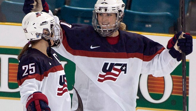 In this Nov. 4, 2014, file photo, Team United States' Monique Lamoureux, right, celebrates her goal against Team Finland with teammate Alex Carpenter at Four Nations Cup women's hockey tournament in Kamloops, British Columbia.