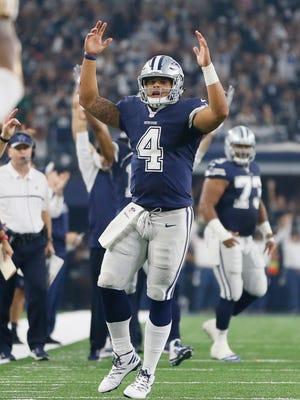 Dallas Cowboys quarterback Dak Prescott (4) celebrates throwing a touchdown in the second quarter against the Washington Redskins at AT&T Stadium.