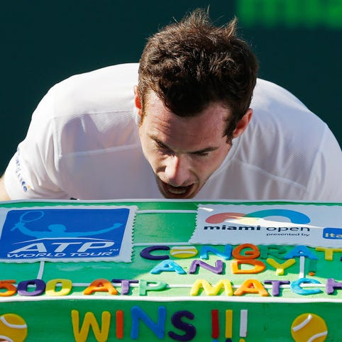 Andy Murray pretends to take a bite of a cake presented