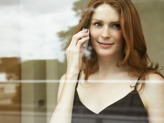 Young woman using mobile phone, smiling, view through window