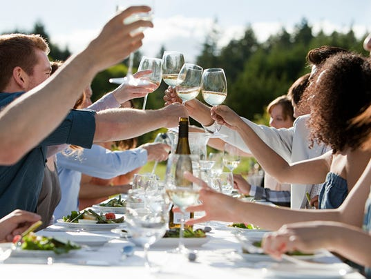 People toasting wine glasses at outdoor dinner party