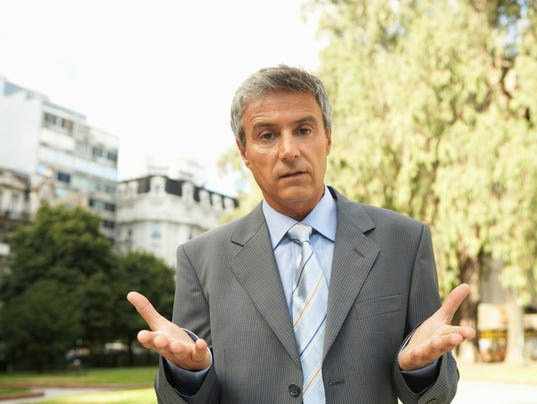 Businessman standing outdoors gesturing, portrait