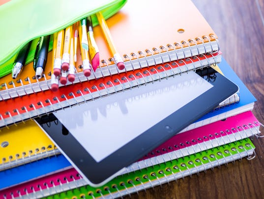 School notebooks in variety of colors with pencils in bag