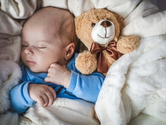Newborn baby boy sleeping together with teddy bear