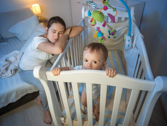 Tired mother got asleep next to baby's crib