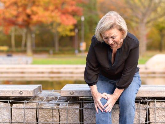 Elderly lady grabbing her knee in pain