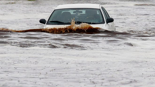 A vehicle tries to navigate a severely flooded street as heavy rains pour down Monday, Sept. 8, 2014, in Phoenix.