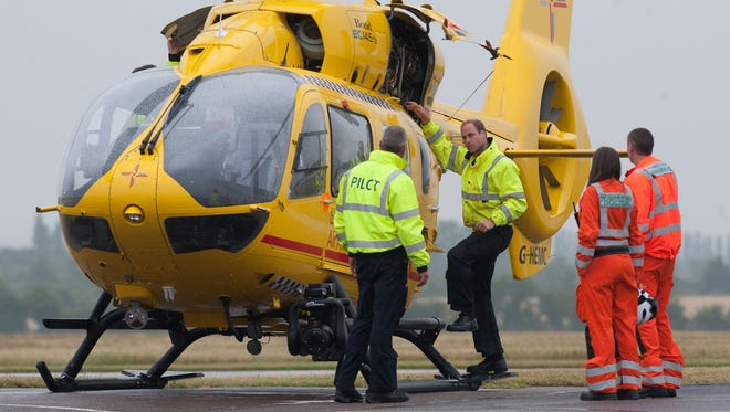 Prince William (2L) prepares to board an air ambulance as part of his work duties.