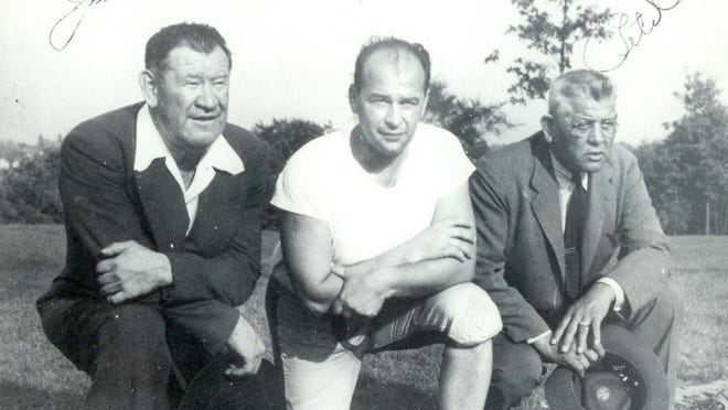 Bup Rearick poses for a photo as McKinley High School head football coach flanked by two early stars of pro football -- Jim Thorpe (left) and Pete Calac (right), who won league titles with the Canton Bulldogs in 1916, 1917 and 1919 -- in an undated photo from the 1940s.