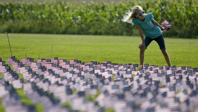 Jordan Giese of Brillion volunteers with her father to help plant 3,000 American flags at the Forest Junction fire department. The flags, part of a 9/11 tribute, will remain on display through Sunday.