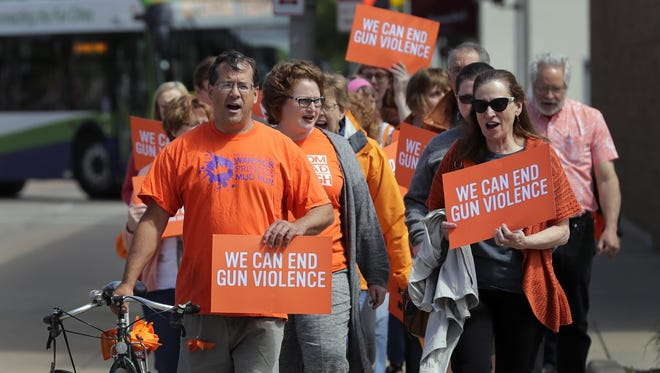 A group of people protest gun violence as the march to  U.S. Rep. Mike Gallagher's office with postcards after a gathering to promote gun safety Friday morning at the Appleton Public Library. About 50 people attended the event, including multiple local officials.