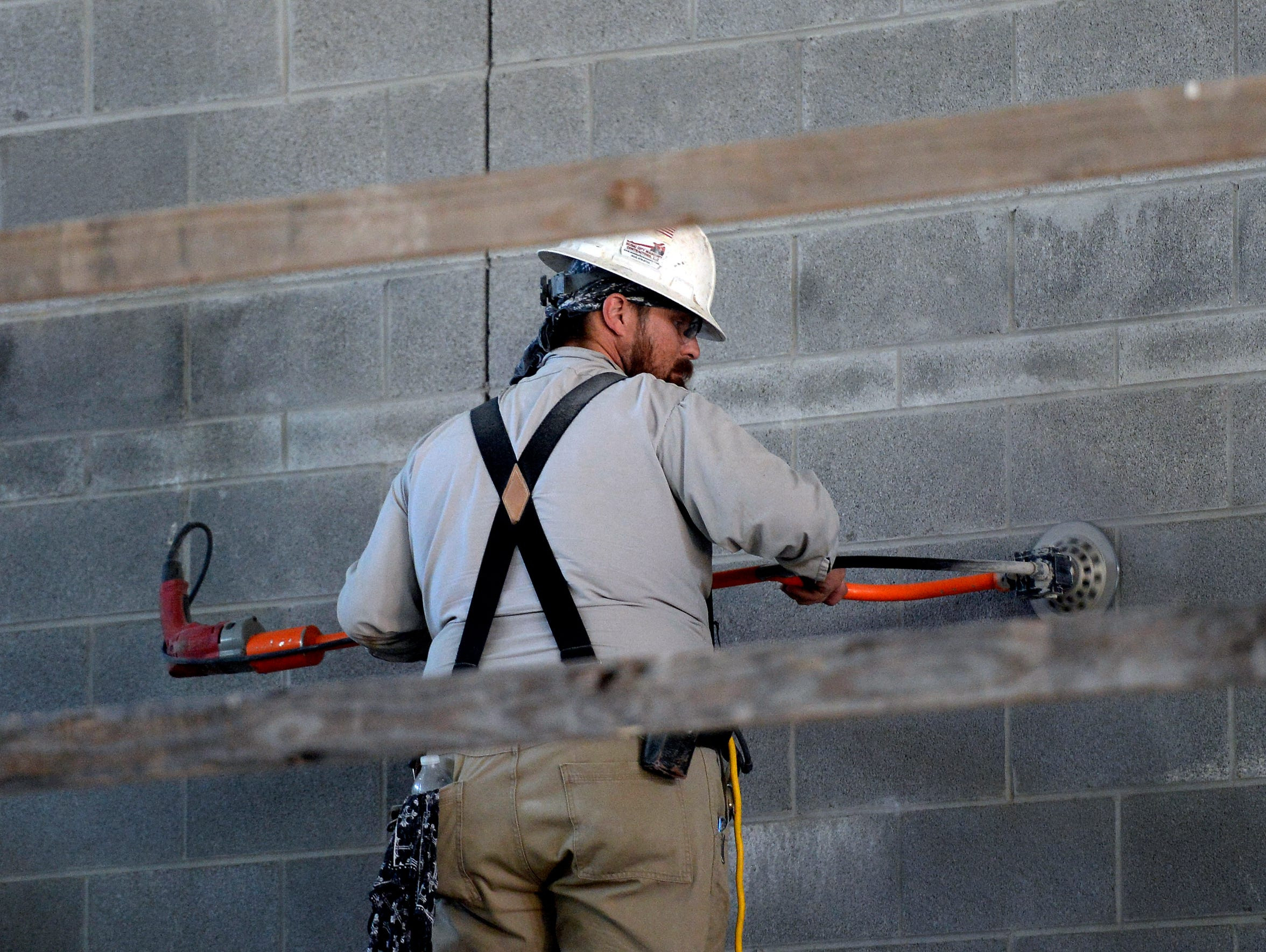 A worker sands concrete blocks in the common area to