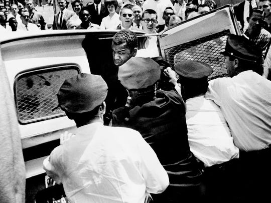 John Lewis, national chairman of the Student Non-Violent Coordinating Committee, gets pushed into the patrol wagon by Metro Police. Lewis was the first demonstrator arrested at Morrison's Cafeteria on West End Ave., April 29, 1964.