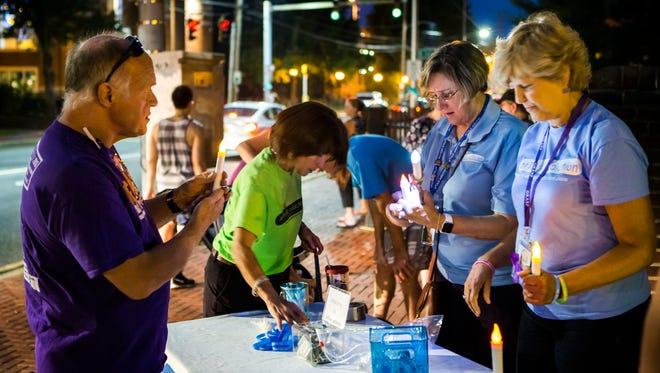 Volunteers pass out electric candles at a vigil for those lost to and suffering from addiction near Old College in Newark on Wednesday night.