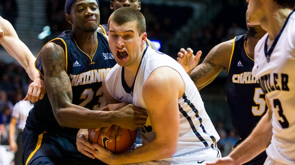 University of Tennessee at Chattanooga forward Tre' McLean (23) and Butler forward Andrew Chrabascz (45) battle for the ball during second half action Tuesday night.