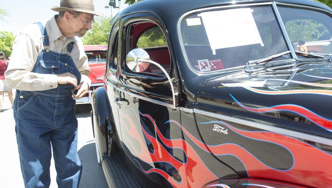 Bob Bailey checks out a 1940 Ford Coupe while browsing the vehicles on display at the Old Town Car Show Saturday, May 30, 2015. Collectors showed off hundreds of hot rods, classic cars and trucks on Walnut Street and E. Mountain Avenue in the annual event.