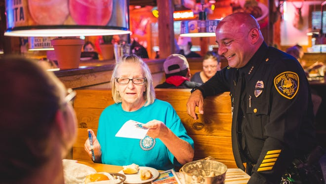 Ellen Isreal, left, speaks to Chief Mike Markle during the Tip-A-Cop event at the Texas Road House in 2016.