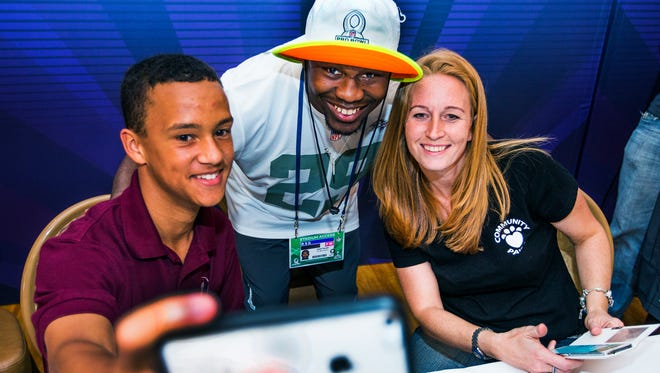 NFL Pro Bowl player Justin Forsett, middle, running back for the Baltimore Ravens, has a selfie made with Donovan Taylor, 15, and his mom, Sarah Taylor, at Luke Air Force Base, Wednesday, January 21, 2015.