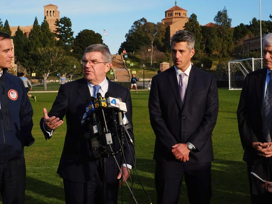 FILE - In this Feb. 1, 2016, file photo, International Olympic Committee President Thomas Bach, second from left, is flanked by Los Angeles Mayor Eric Garcetti, left, LA 2024 chairman Casey Wasserman, second from right, and UCLA chancellor Gene Block, right, during a news conference in Los Angeles. As the IOC moves the goalpost in the 2024 Olympic contest, bid leaders from Los Angeles and Paris head to a campaign event in Denmark on Tuesday, April 4, 2017 unsure of exactly what they are shooting for. (AP Photo/Richard Vogel, File)