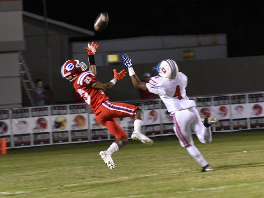 Evangel's Josh Walker goes high for the ball in their playoff game Friday against Rummel.