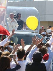 Pope Francis blesses the crowd as he travels the streets of Juárez on Wednesday.