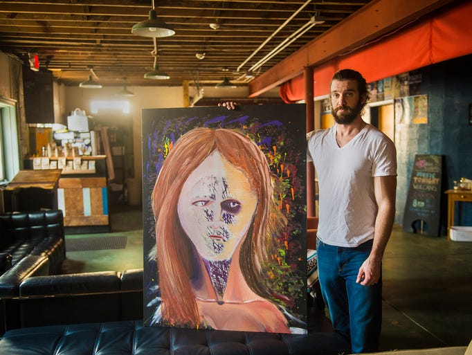 Artist Tim Smith, 31, stands with his work entitled