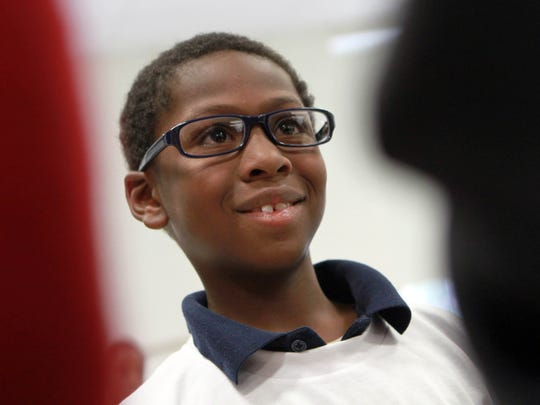 Marquan Clark, a third grader at Shortlidge Elementary School, receives a free pair of reading glasses from the Vision to Learn program on Thursday.