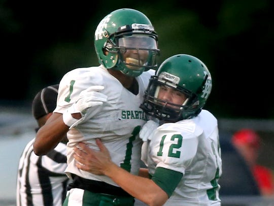White Station's Dillon Mitchell, left, and Burk Williams, right, celebrate Mitchell's touchdown against Oakland on the first play of the game at Oakland, on Friday, August  2, 2014.