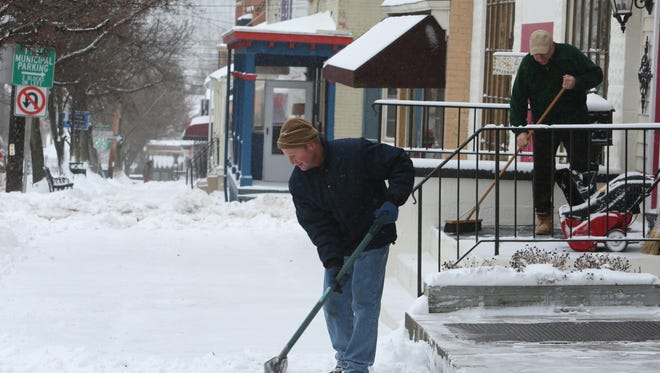 Tom Hopper clears a sidewalk in Cold Spring Jan. 27, 2015. Snow accumulation was much less than expected after a major storm tracked about 50 miles east of it's predicted path.