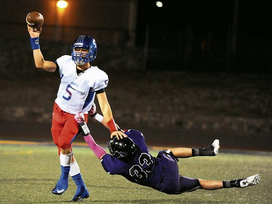 Franklin's William Hulshof attempts to bring down Americas' quarterback Orlando Garcia, during a 2013 game at Coronado High School.