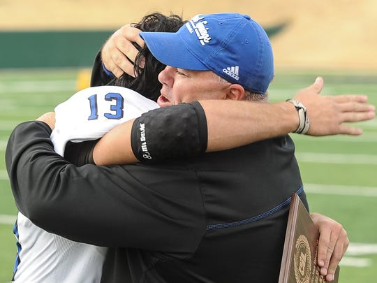 Richland Springs head coach Jerry Burkhart embraces spread back Chance Bush after the Coyotes' win over Follett in the 2012 state final.