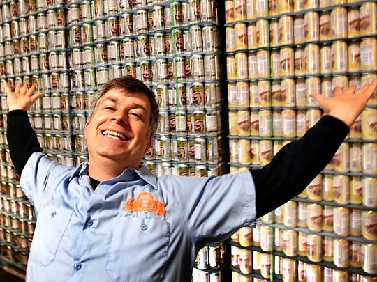 Sun King co-owner Dave Colt poses in front of a wall of beer cans in 2010.