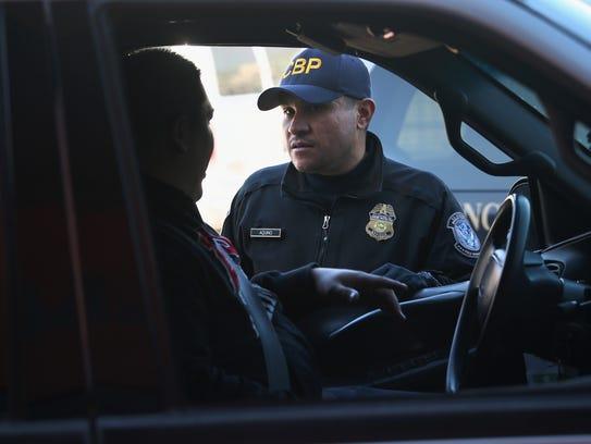 Un oficial del CBP interroga a una persona en la frontera.