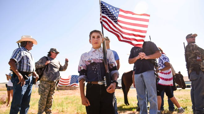 J.P. Thornsley, 12, carries a U.S. flag in the barrel of his 20-gauge shotgun before leading about 250 gun rights advocates in an open carry demonstration <137>during the Independence Day parade <137>in Westcliffe, Colo. Colorado and Ohio are among 29 states that allow residents to open carry handguns without a permit. <137>on Friday, July 4, 2014. (AP Photo/The Gazette, Michael Ciaglo)<137>