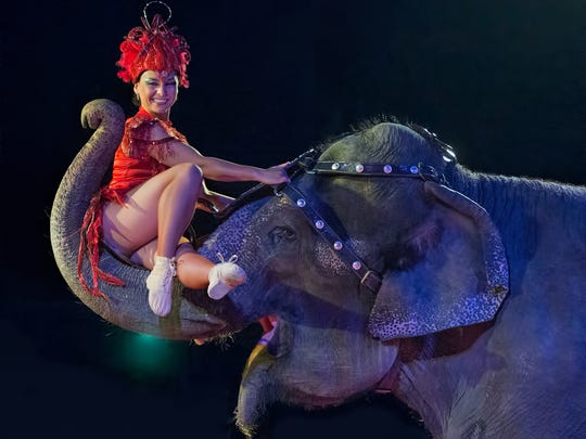 Cindy the elephant carries circus performer Deya Rosales with her trunk at Kelly Miller Circus.