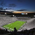 """The sun sets over a """"Whiteout"""" crowd at Beaver Stadium. Attendance at PSU home games was down slightly in 2015"""